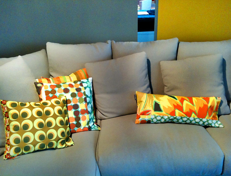 Grafische Prints in Leuchtfarben möbeln das graue Sofa auf