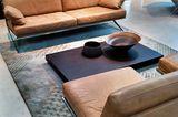Leder, Holz und Metall in warmen, matten Brauntönen
