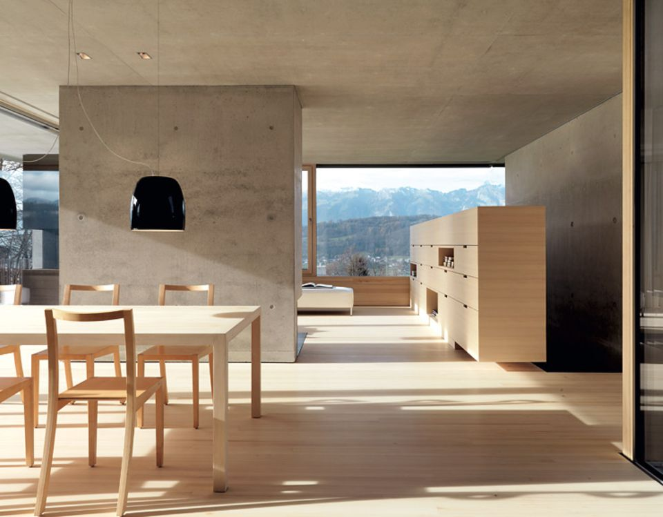 Wände aus grauem Sichtbeton treffen auf einen Fußboden aus Weißtanne und Möbel, die ebenfalls aus hellen Hölzern gefertigt sind. Der Effekt: warmes Holz und grauer Beton ergänzen sich perfekt und wirken wohnlich. (Zum Rundgang durch dieses Architektenhaus).