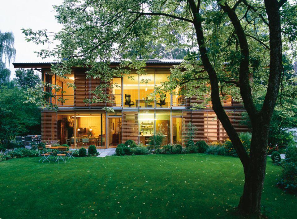 Holzhaus mit Lamellen aus Lärchenholz und gläserner Fassade