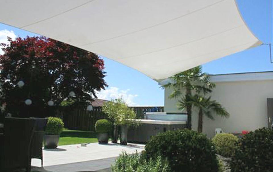 Maßgefertigte Sonnensegel spenden Schatten auf der ganzen Terrasse.