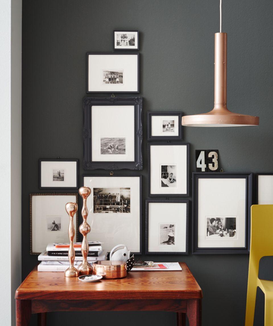 Die Bilder hängen sehr eng nebeneinander, das sieht modern und aufgeräumt aus. Tipp: Fotos und Schilder auf die Oberkante eines Bilderrahmens stellen – dort haben sie Platz zum Wirken.