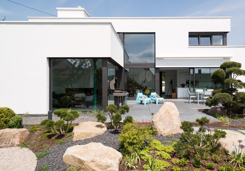 Der wohlproportionierte rechtwinklige Bau öffnet sich über großflächige Fenster zur Terrasse und zum anspruchsvoll gestalteten Garten.