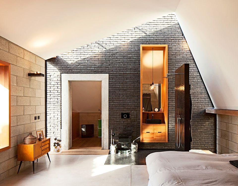 Im Obergeschoss unter dem markanten spitzen Winkel der Dachkonstruktion befindet sich das Elternschlafzimmer mit integriertem Bad.