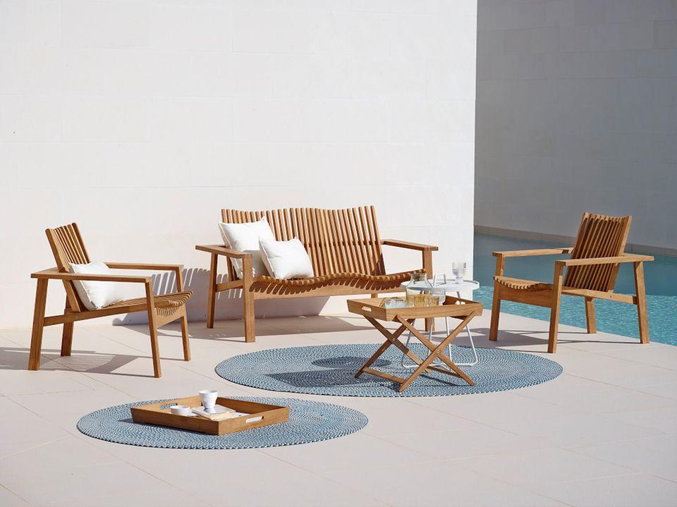 Sitzgruppen aus Holz und witterungsbeständige Outdoorteppiche bringen Wohnlichkeit auf die Terrasse.