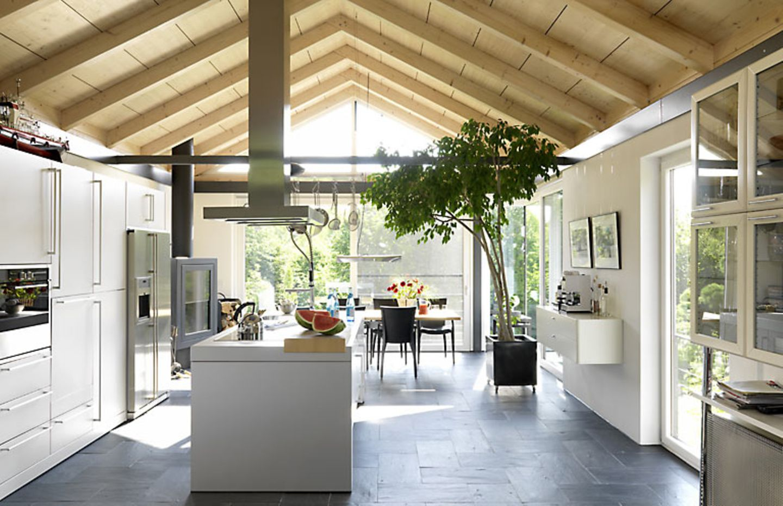 Eine offene Küche ist der Treffpunkt jeder Wohnung. Hier wirkt die Wohnküche durch die offene Dachkonstruktion und die Kochinsel in der Mitte noch wohnlicher.