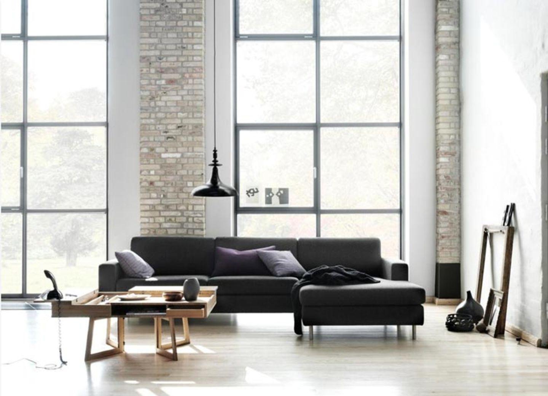 Zeitlos: Weiße Wände, schwarze Sitzmöbel und Möbel aus Holz