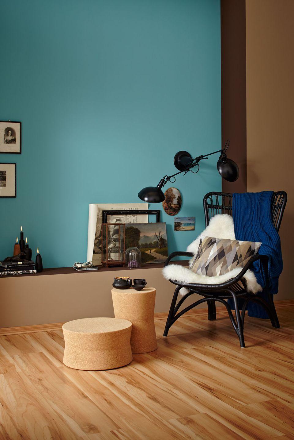 Wandfarbe Petrol, Rattansessel in Schwarz und Hocker aus Kork