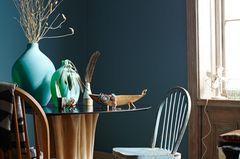 Wandfarbe in Petrol, runder Esstisch und Stühle aus Holz