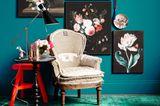 Bilder an einer Wand in Petrol und Sessel, Beistelltisch und Hocker