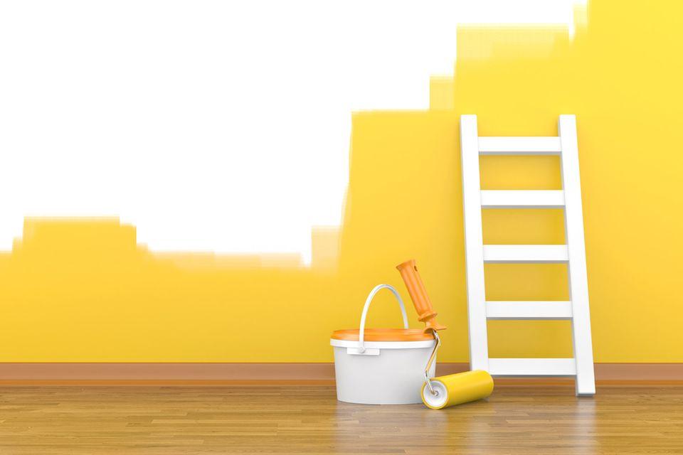 Ein Farbeimer und eine Leiter stehen vor einer halb gestrichenen Wand