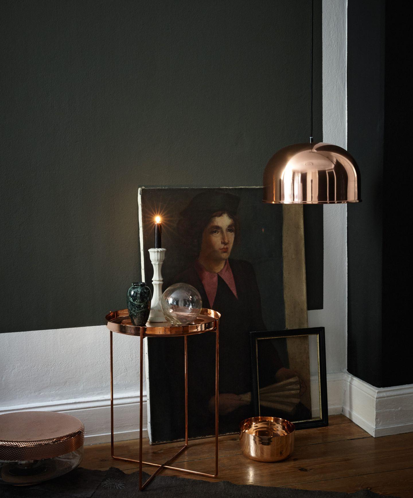 Möbel und Accessoires aus Kupfer vor Wand in Schwarz