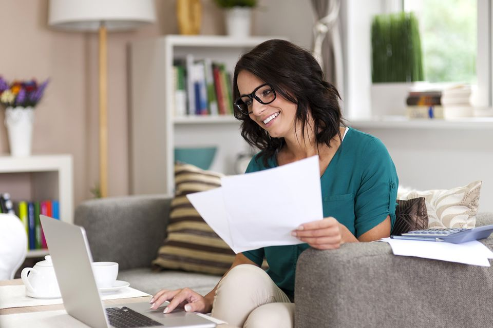 Frau mit Ausdrucken in der Hand sitzt vorm Laptop