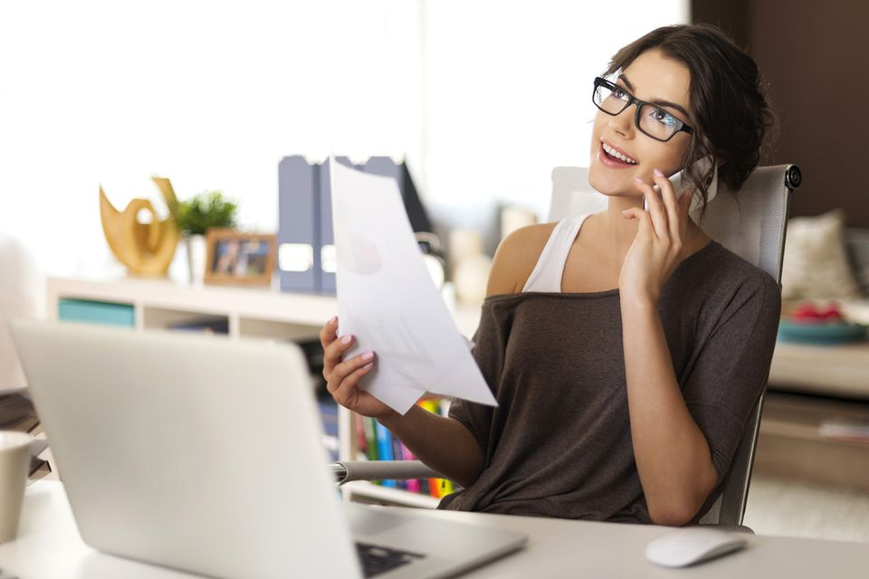 Attraktive junge Frau telefoniert vorm Notebook