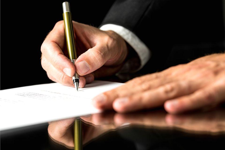 Mann im Anzug unterschreibt die Kündigung eines Mietvertrags
