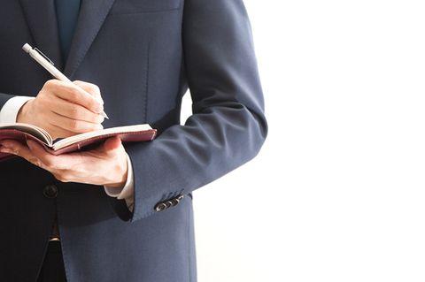 Mann im Anzug macht sich Notizen
