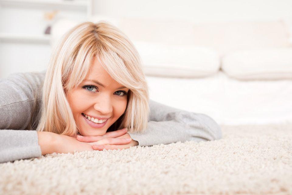Eine junge Frau liegt auf einem hellen Teppichboden