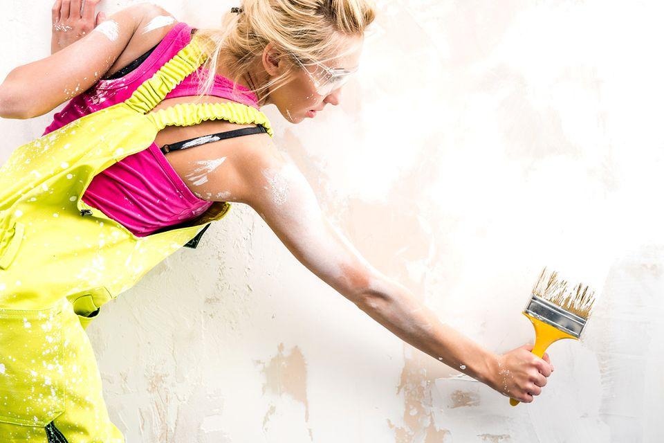 Frau in gelber Arbeitshose streicht eine verputzte Wand