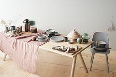Gedeckter Tisch mit Kermaik und Tischwäsche in sanften Farbtönen