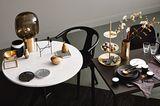Lässig gedeckter Tisch mit Messing, Schwarz, Marmor und winterlichen Zweigen.