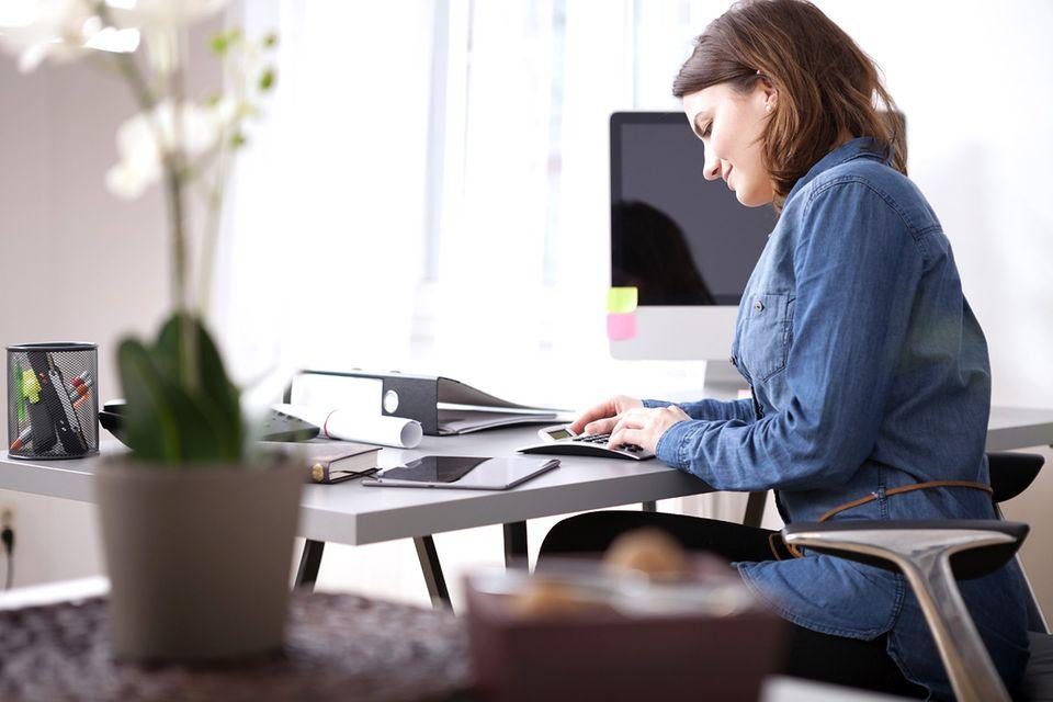 Frau mit Taschenrechner sitzt am Schreibtisch