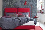 Doppelbett in Rot mit grauer Bettwäsche vor einer grauen Wand