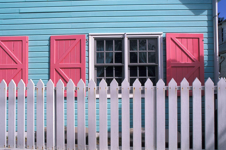 Hellblaues Haus mit rose Fensterläden und weißem Holzzaun