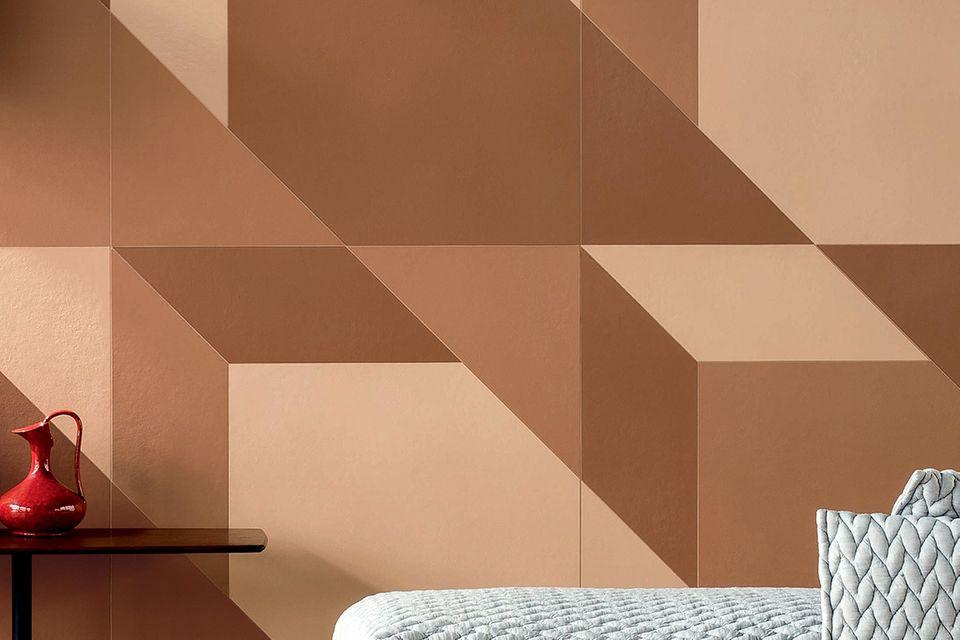 Tarrakottafarbene Wand mit angedeutetem Sessel und Sideboard davor
