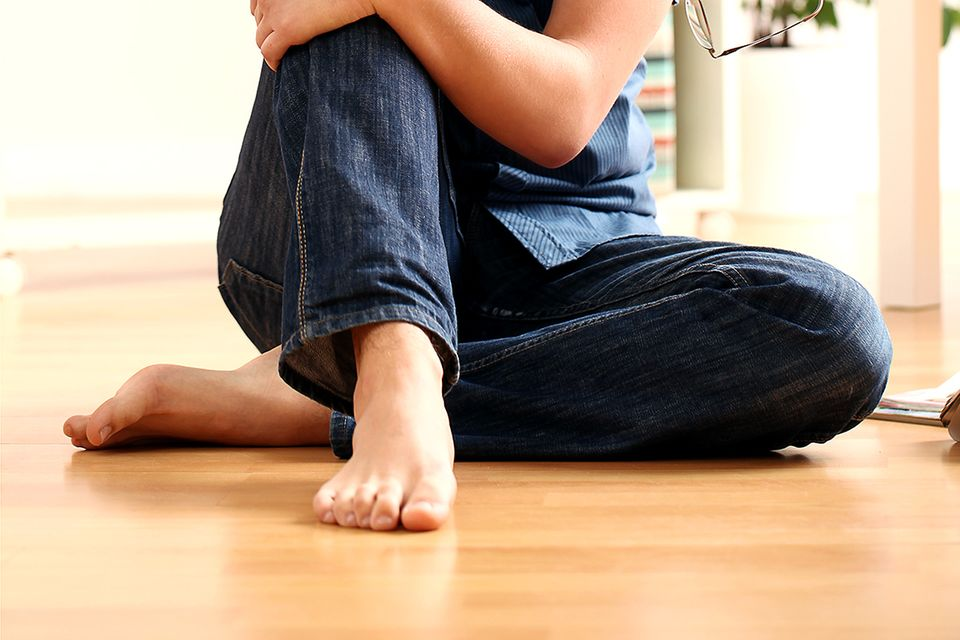 Mann in Jeans sitzt barfuß auf Laminatboden