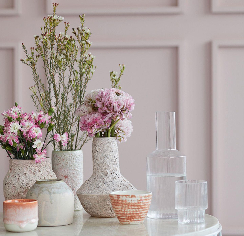 Vasen aus Keramik und Glas vor rosafarbener Wand