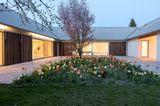 Reduzierter Neubau mit grünem Innenhof: Garten im Hof