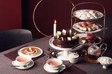 Weihnachtlich gedeckte Kaffeetafel in Rot- und Violetttönen