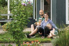 Familie vor Gartenlaube im Schrebergarten