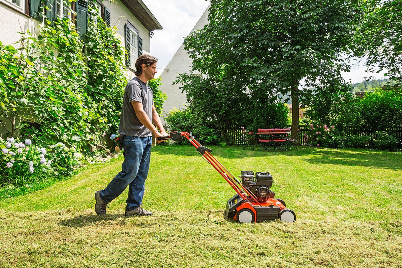 Mann vertikutiert Rasen