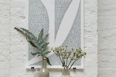 Wohnen in Weiß - grafisches Poster vor einer weiß gestrichenen Backsteinwand