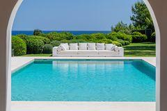 Ibiza: Blick durch die Arkaden auf einen Pool mit langem Outdoorsofa