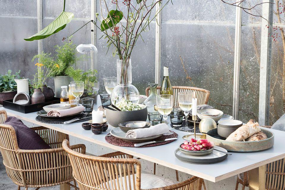 Gedeckter Tisch mit Korbstühlen