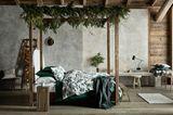 Hütten-Zauber zu Weihnachten im Schlafzimmer - mit Tannendeko, Lichterketten, Holz und Sichtbeton