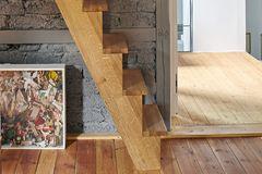Die Stiege aus Holz steht im Kontrast zur grauen Wand