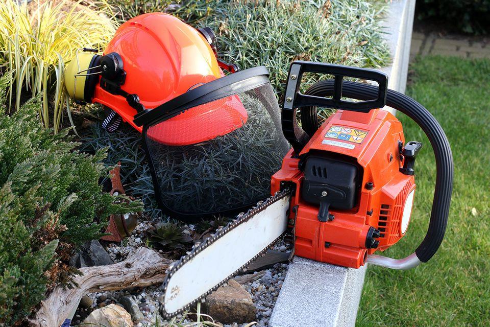 Ausrüstung zum Baum fällen - Schutzhelm und Motorsäge