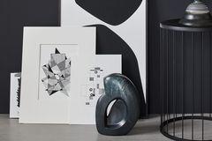 Schwarz-weiße Kunstdrucke vor schwarzer Wand