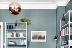 Wohnzimmr mit schlichten Regalen und grüner Wand