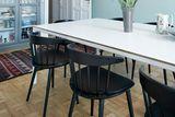 Esszimmer mit weißen Esstisch und schwarzen Stühlen