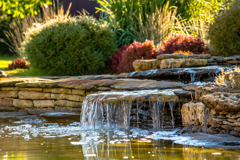 Wasserlauf, der in einen Gartenteich fließt