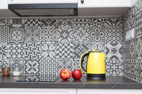 Gelber Wasserkocher vor gefliester Küchenrückwand