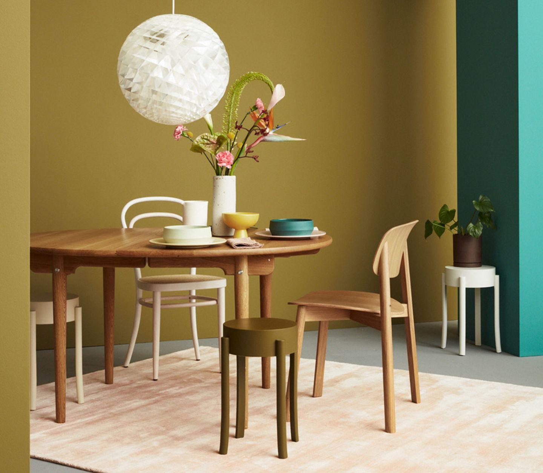Esszimmer mit Holzmöbeln und Grüntönen im Hintergrund