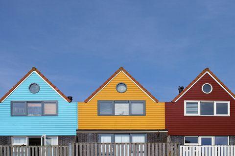 Drei Häuser in Hellblau, Gelb und Dunkelrot, die nebeneinander stehen