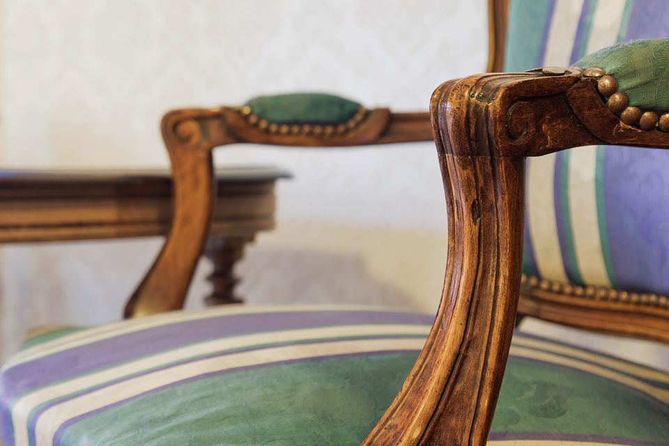 Antiker Holzstuhl mit blau-grün-weißer Polsterung vor antikem Schreibtisch