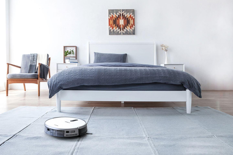 Saugroboter Deebot 710 von Ecovacs beim Saugen eines Teppichs in einem Schlafzimmer.