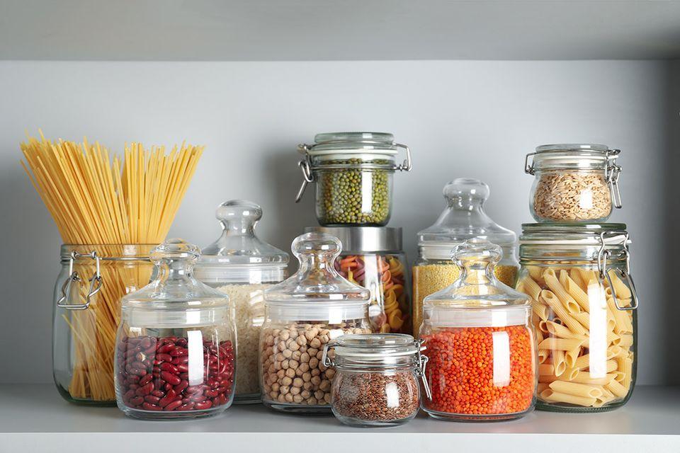 In Vorratsgläser umgefüllte Lebensmittel wie Reis, Kichererbsen, Leinsamen und mehr